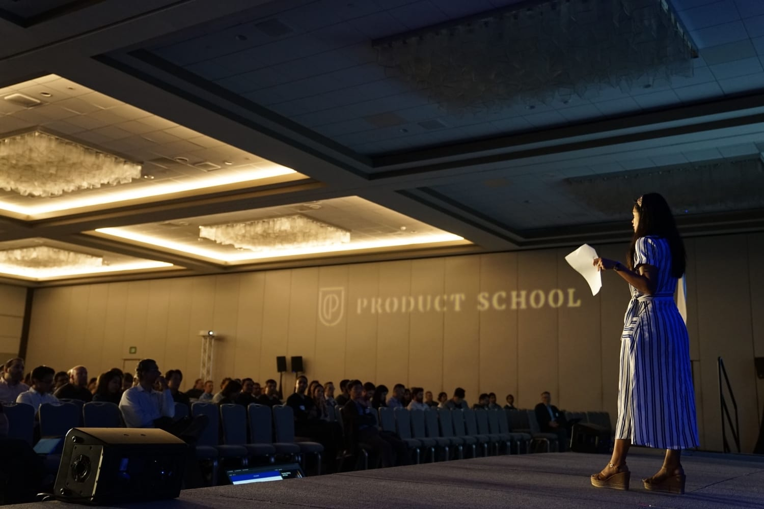 woman speaking on stage at a conference